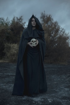Długi portret mężczyzny ubranego jak mroczny mag z czaszką