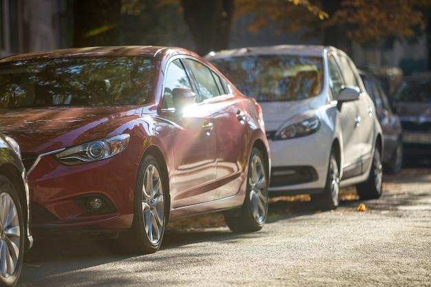 Długi rząd różnych błyszczących samochodów osobowych i dostawczych zaparkowanych wzdłuż pustego pobocza drogi w słoneczny jesienny dzień na tle niewyraźne zielone złote liście bokeh. nowoczesny styl życia miasta, koncepcja problemu parkowania pojazdów.