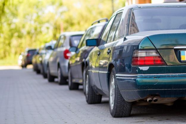 Długi rząd samochodów zaparkowanych w spokojnej okolicy na czystej, pustej, brukowanej ulicy na pięknych zielonych drzewach w jasny, słoneczny letni lub letni dzień.