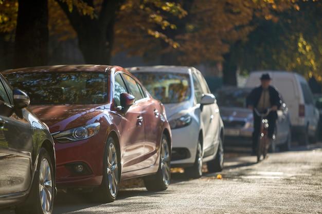 Długi rząd samochodów zaparkowanych wzdłuż pustego pobocza