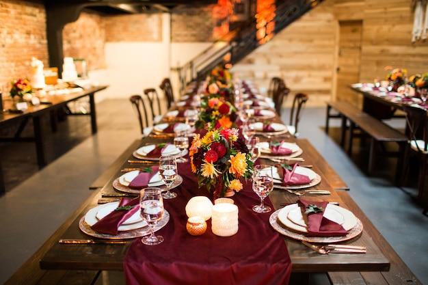 Długi stół z luksusowymi talerzami i ozdobiony kolorowymi kwiatami i świecami