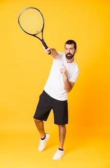 Długi strzał bawić się tenisa nad odosobnionym żółtym tłem mężczyzna