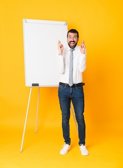 Długi strzał biznesmen daje prezentaci na białej desce nad odosobnioną kolor żółty ścianą z palców krzyżować