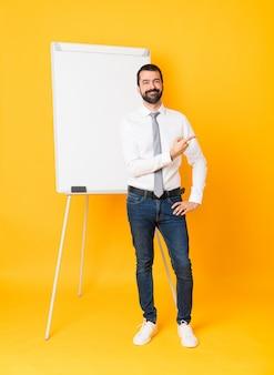 Długi strzał biznesmen daje prezentaci na białej desce nad odosobnionym żółtym tłem wskazuje strona przedstawiać produkt