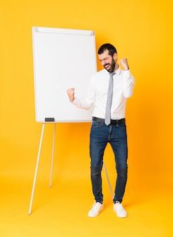 Długi strzał biznesmen daje prezentaci na białej desce świętuje zwycięstwo na odosobnionym żółtym tle