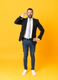 Długi strzał biznesowy mężczyzna nad odosobnionym kolorem żółtym z szkłami i zaskakujący