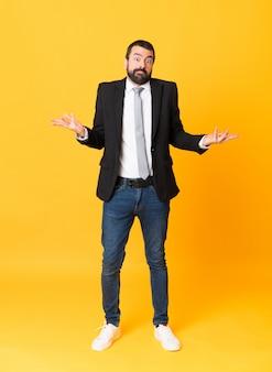 Długi strzał biznesowy mężczyzna nad odosobnionym żółtym tłem robi wątpliwość gestowi