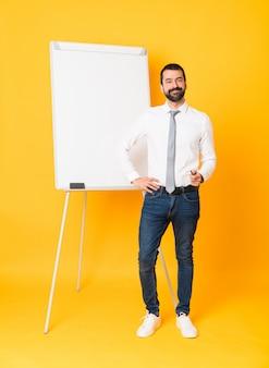 Długi strzał daje prezentaci na białej desce biznesmen nad odosobnionym żółtym tłem pozuje z rękami przy modnym i uśmiechniętym biznesmenem