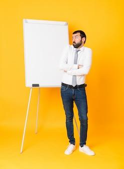 Długi strzał daje prezentaci na białej desce biznesmen nad odosobnionym żółtym tłem robi wątpliwość gestowi podczas gdy podnoszący ramiona
