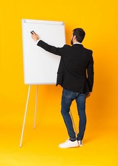 Długi strzał daje prezentaci na białej desce biznesmen nad odosobnionym żółtym tłem
