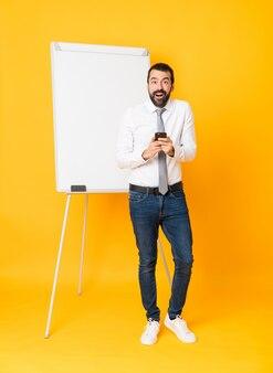 Długi strzał daje prezentaci na białej desce biznesmen