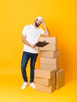 Długi strzał doręczeniowy mężczyzna wśród pudeł nad odosobnionym żółtym tłem
