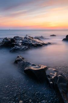 Długi strzał ekspozycji seascape na guernsey podczas zachodu słońca