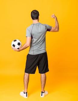 Długi strzał gracza futbolu mężczyzna nad odosobnionym kolorem żółtym