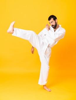 Długi strzał mandoing karate nad odosobnionym kolorem żółtym