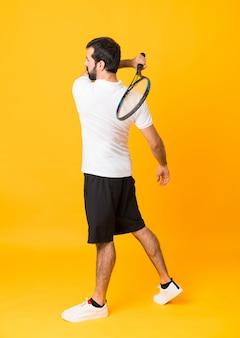 Długi strzał mężczyzna bawić się tenisa nad kolorem żółtym