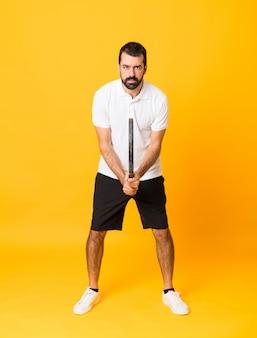 Długi strzał mężczyzna nad odosobnionym kolorem żółtym bawić się tenisa