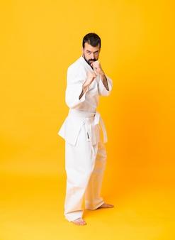 Długi strzał mężczyzna nad odosobnionym żółtym robi karate