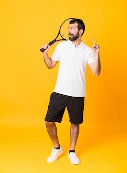 Długi strzał mężczyzna nad odosobnionym żółtym tłem bawić się tenisa i wskazuje up
