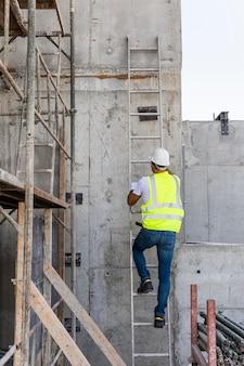 Długi strzał mężczyzna wchodzący po schodach na placu budowy