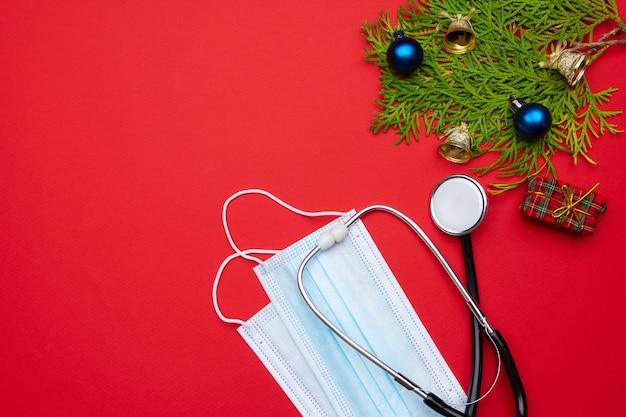 Długi, szeroki sztandar świąteczny z dekoracjami świątecznymi, stetoskopem medycznym i maseczkami na twarz na czerwonym tle. kartkę z życzeniami świątecznymi dla koncepcji medyków.