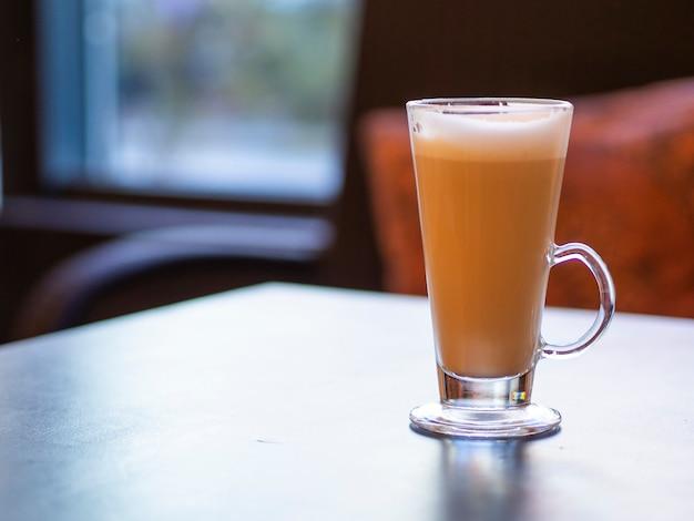 Długi szklany kubek cappuccino na drewnianym stole z miejsca na kopię