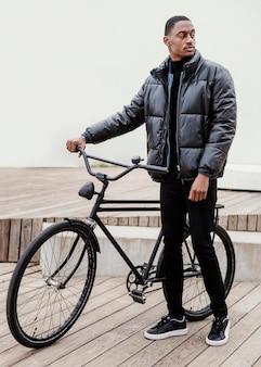 Długi widok człowieka z rowerem
