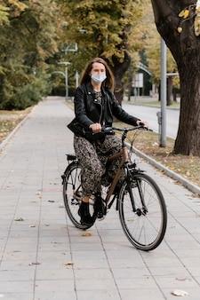 Długi widok kobiety noszącej maskę i jazdy na rowerze