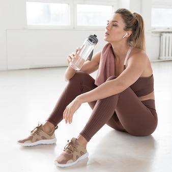 Długi widok kobiety obsiadanie w gym