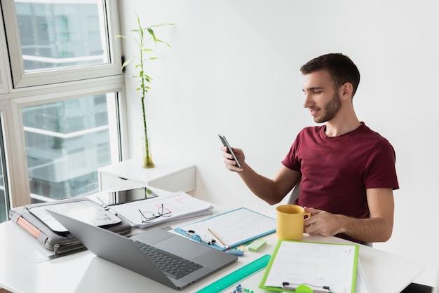 Długi widok mężczyzna siedzi przy biurowym biurkiem