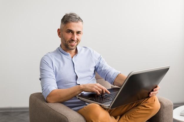 Długi widok mężczyzna używa jego laptop i ono uśmiecha się