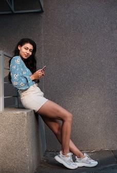Długi widok trzyma jej telefon kobieta
