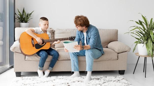 Długi widok uczeń i nauczyciel gra na gitarze