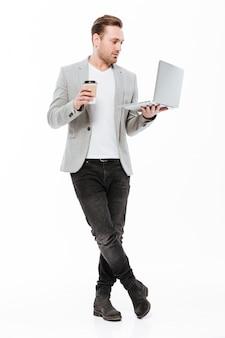 Długi wizerunek młody przedsiębiorca w kurtki pozyci z srebnym laptopem i wynos kawą w rękach, odizolowywający nad biel ścianą