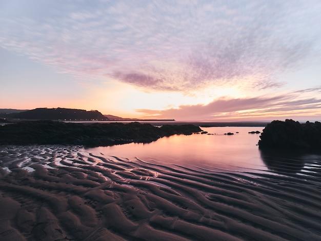 Długi zachód słońca ze skałami na pierwszym planie skąpanym przez jedwabistą wodę i odbicie słońca.