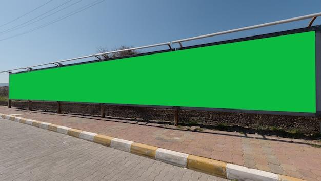 Długi zielony ekran do wyświetlania reklam na poboczu drogi, doskonałe miejsce na tekst