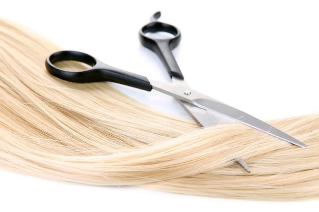 Długie blond włosy i nożyczki na białym tle