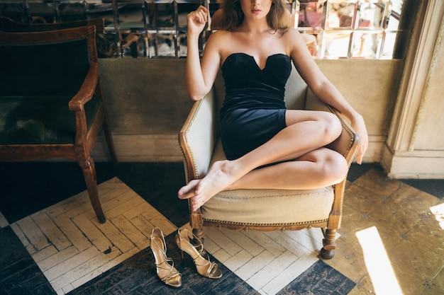 Długie chude nogi boso z sandałami na wysokim obcasie, modne detale eleganckiej pięknej kobiety siedzącej w kawiarni vintage w czarnej aksamitnej sukience, bogata stylowa dama, eleganckie modne obuwie