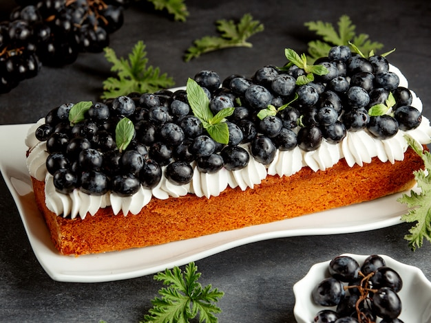 Długie ciasto ozdobione białą śmietaną i jagodami