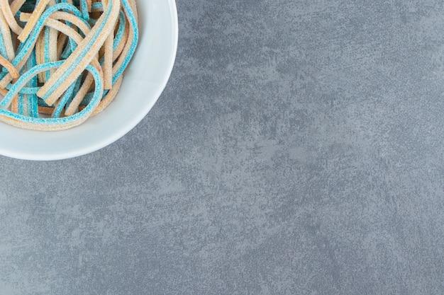 Długie cukierki do żucia w białej misce.