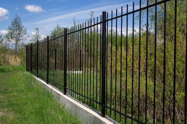 Długie czarne przezroczyste metalowe ogrodzenie z betonową podstawą przeciw błękitne niebo. układ ukośny.