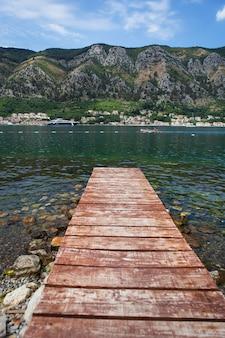 Długie drewniane molo na tle pięknej zatoki kotorskiej, czarnogóra. bardzo piękna promenada i plaża z czystą, błękitną wodą.