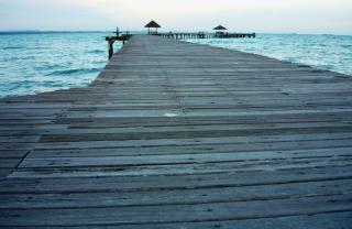 Długie, drewniane molo o zachodzie słońca tropikalne niebo