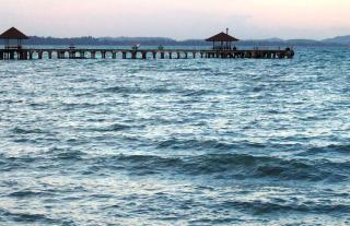 Długie, drewniane molo o zachodzie słońca tropikalne