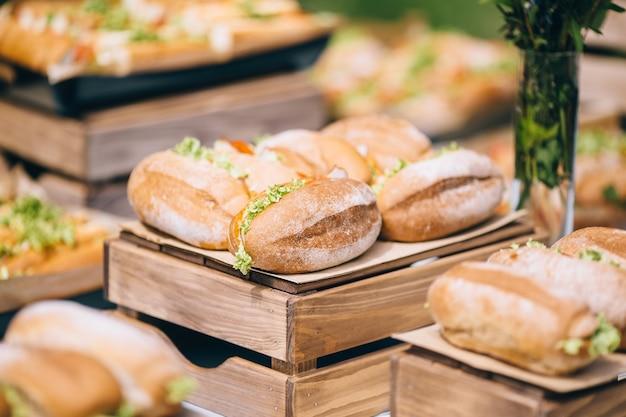 Długie kanapki ciabatta z sałatą, plastrami świeżych pomidorów, ogórkiem, szynką, salami i serem
