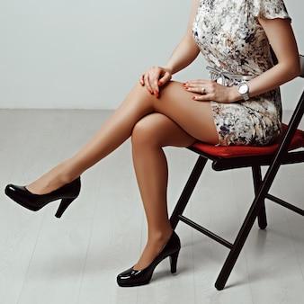 Długie kobiece nogi w jasnobrązowych rajstopach i wysokich obcasach siedzących na stołku