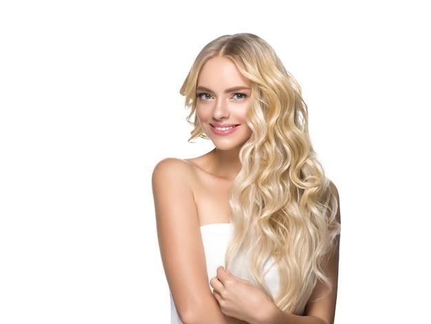 Długie kręcone blond włosy kobieta ze zdrową skórą i naturalnym makijażem na białym tle. strzał studio.