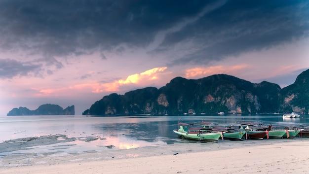 Długie łodzie stoją na wyspie phi phi. różowy zachód słońca nad wyspami.