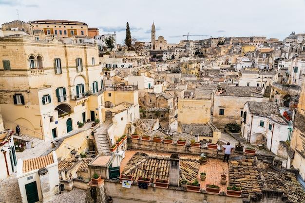 Długie, panoramiczne widoki na skaliste stare miasto matera z kamiennymi dachami.