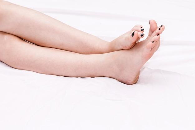 Długie perfect kobiet nogi na białym łóżku